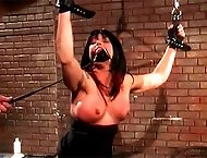 Gagged slave has her hands chained up so her big, round tits can be slapped with a crop